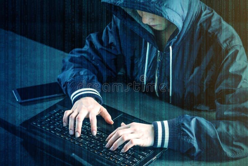 黑客青少年使用一台膝上型计算机乱砍系统 恶意病毒的创作和传染 网络罪行的概念 免版税库存照片