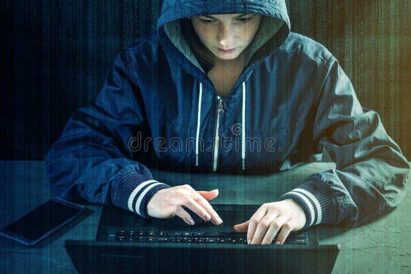 黑客青少年使用一台膝上型计算机乱砍系统 窃取个人和恶意病毒的传染 网络罪行的概念 库存图片
