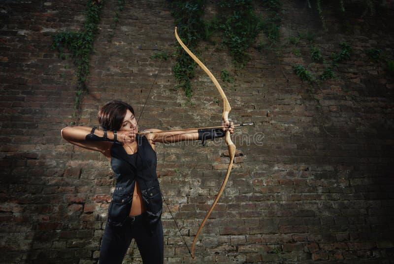 黑射击的运动深色的女孩从弓 免版税库存照片