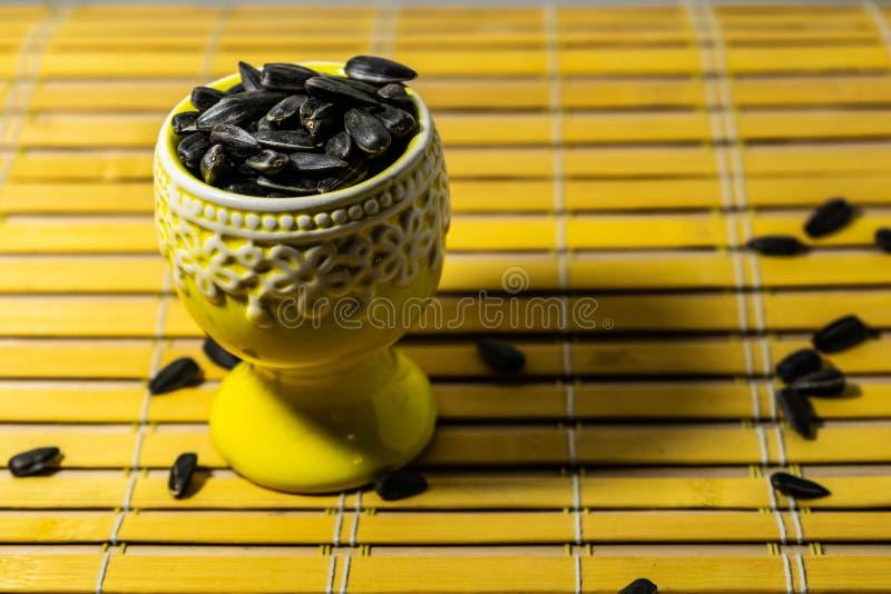 黑小向日葵种子 点击与果壳的种子 在一个黄色微型立场的极少数在一块木餐巾 溢出了有些种子 免版税图库摄影