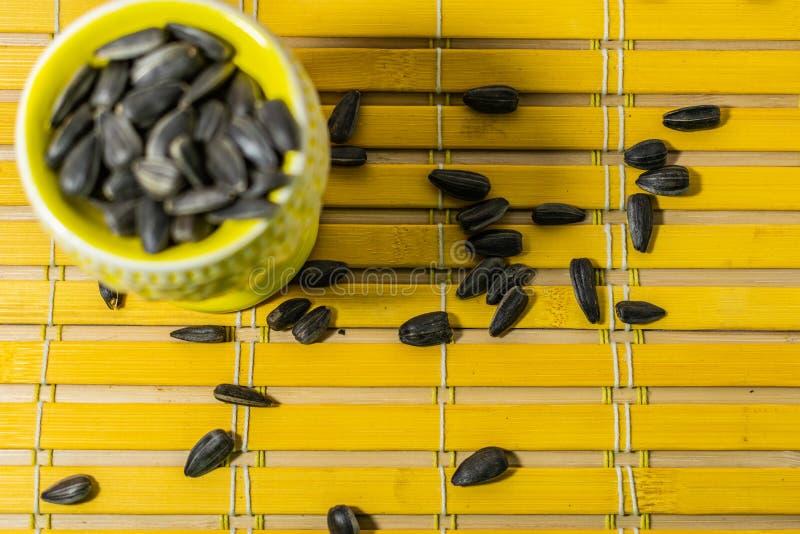 黑小向日葵种子 点击与果壳的种子 在一个黄色微型立场的极少数在一块木餐巾 溢出了有些种子 库存照片
