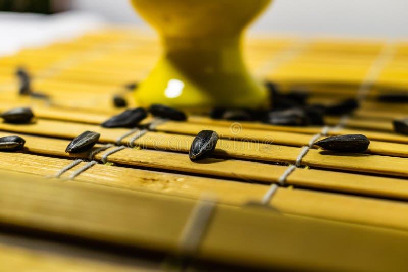 黑小向日葵种子 点击与果壳的种子 在一个黄色微型立场的极少数在一块木餐巾 溢出有些种子 库存照片