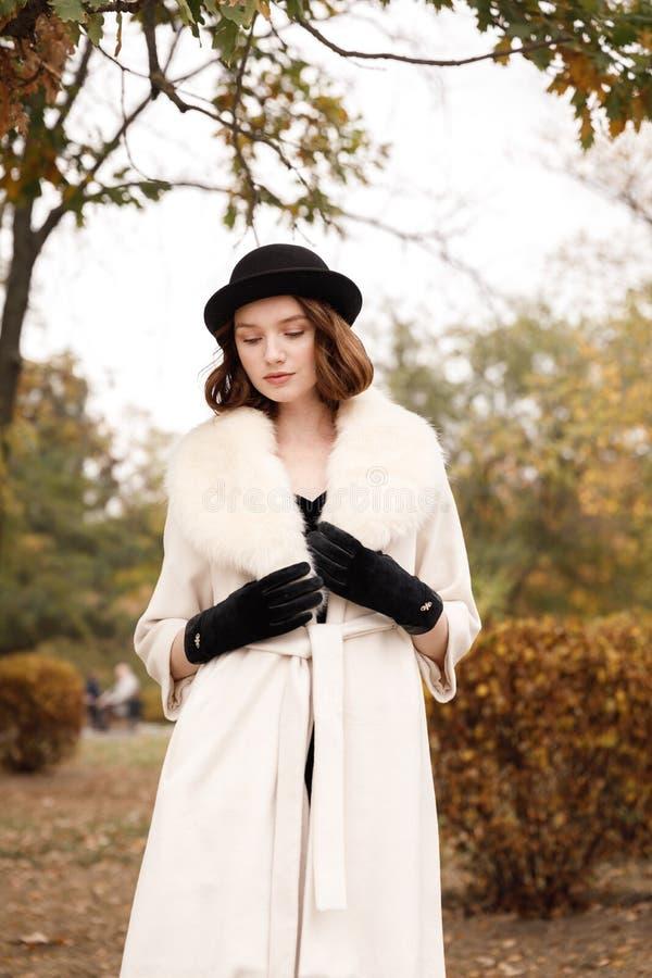 黑帽会议的减速火箭的匪徒女孩,皮大衣和黑手套在秋天停放 免版税库存照片