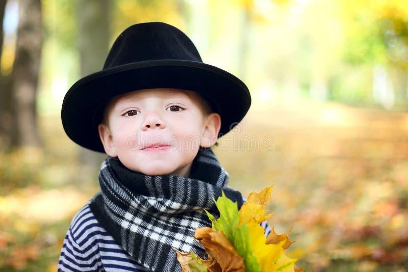 黑帽会议的小逗人喜爱的绅士在秋天公园 免版税图库摄影