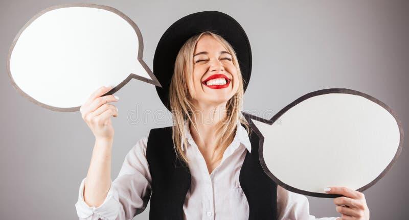 黑帽会议的愉快的快乐的微笑的红色嘴唇行家妇女有讲话bubles的 免版税图库摄影