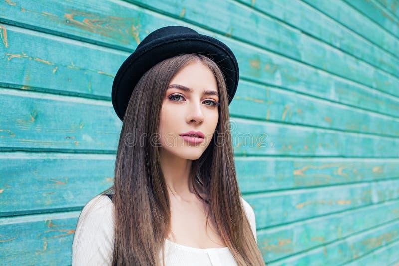 黑帽会议的美丽的年轻女人在蓝色木背景 免版税库存图片
