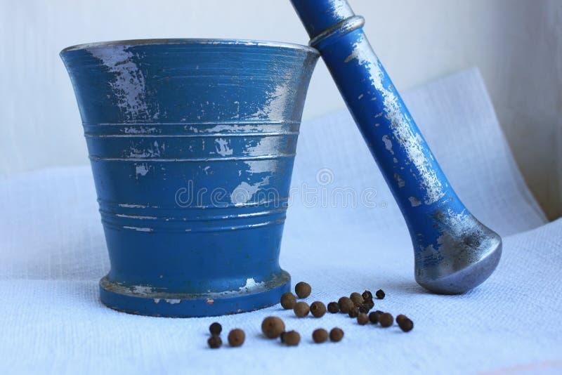 黑干胡椒和多香果在古老金属灰浆与杵在亚麻制背景 免版税图库摄影