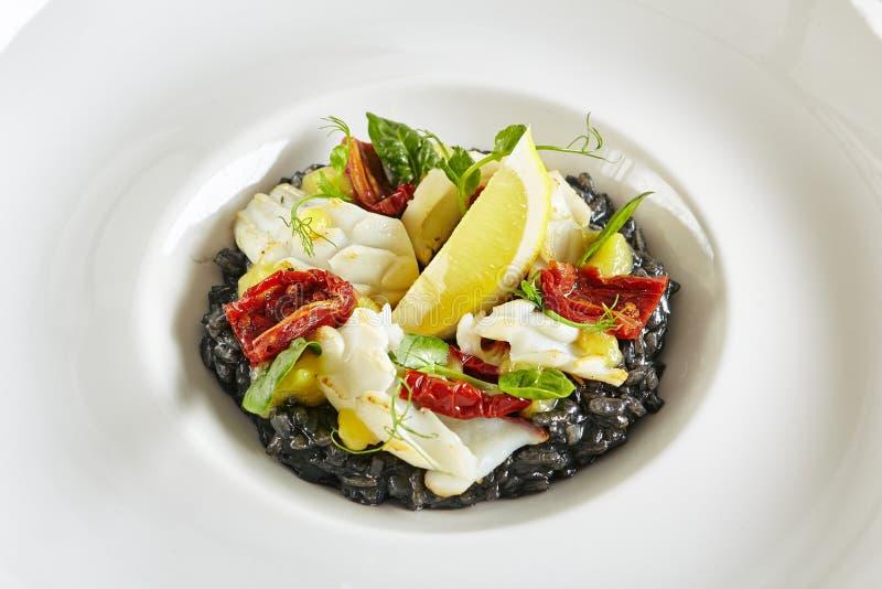 黑意大利煨饭用章鱼和各式各样的蕃茄 免版税库存图片