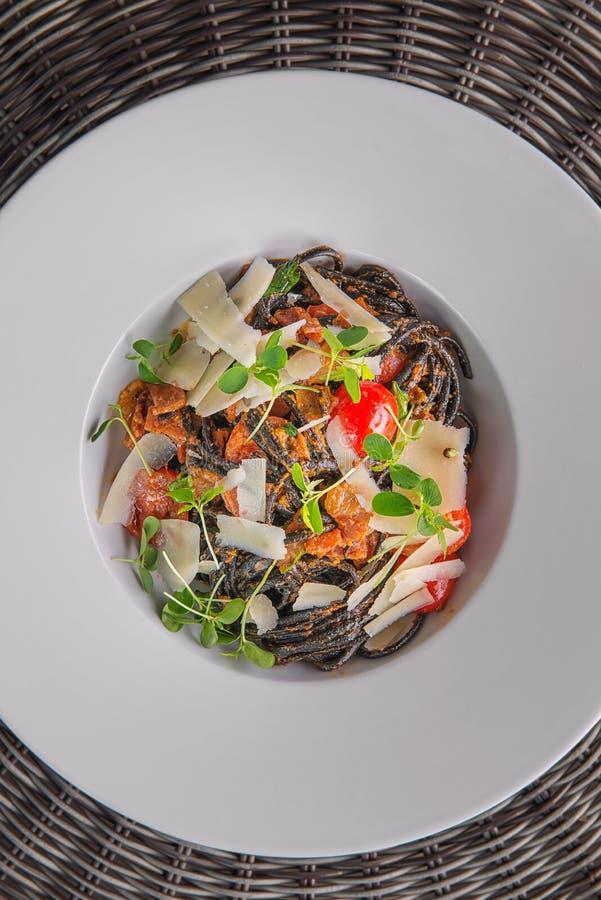 黑意大利面团用西红柿酱和巴马干酪,供食在白色板材、产品摄影餐馆的和美食术 图库摄影