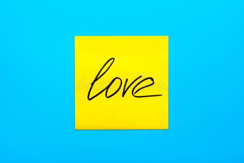 黑手写的题字爱的关闭在蓝色背景的一个黄色方形的贴纸与拷贝spase 库存照片