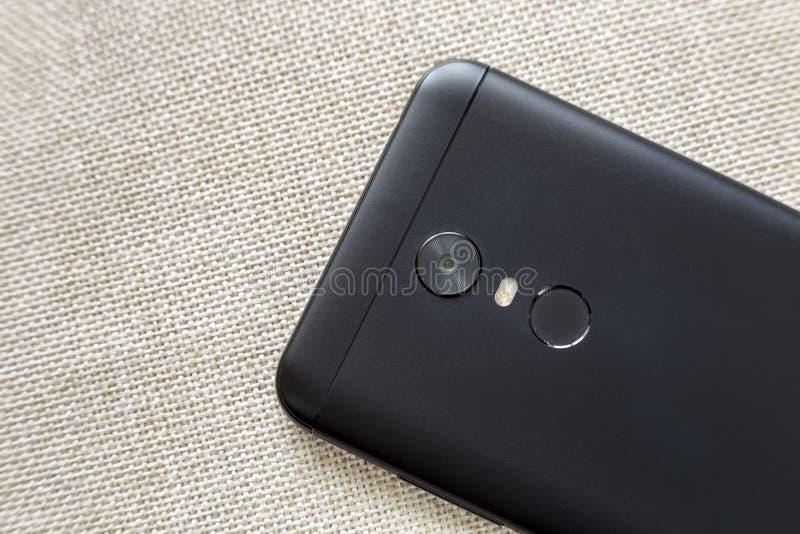 黑手机的后部隔绝与安全拇指指纹扫描装置、照相机和闪光照明设备在轻的布料 免版税图库摄影