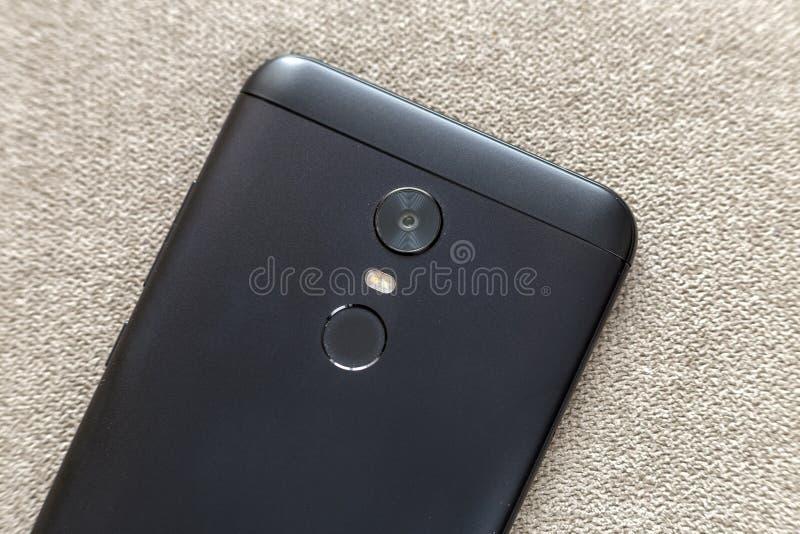 黑手机的后部隔绝与安全拇指指纹扫描装置、照相机和闪光照明设备在轻的布料 免版税库存照片