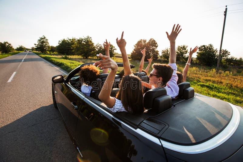 黑敞蓬车在乡下公路 愉快的小组少女和人在汽车坐停滞他们的手 免版税库存照片