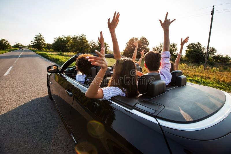 黑敞蓬车在乡下公路 愉快的小组少女和人在汽车坐停滞他们的手 库存图片