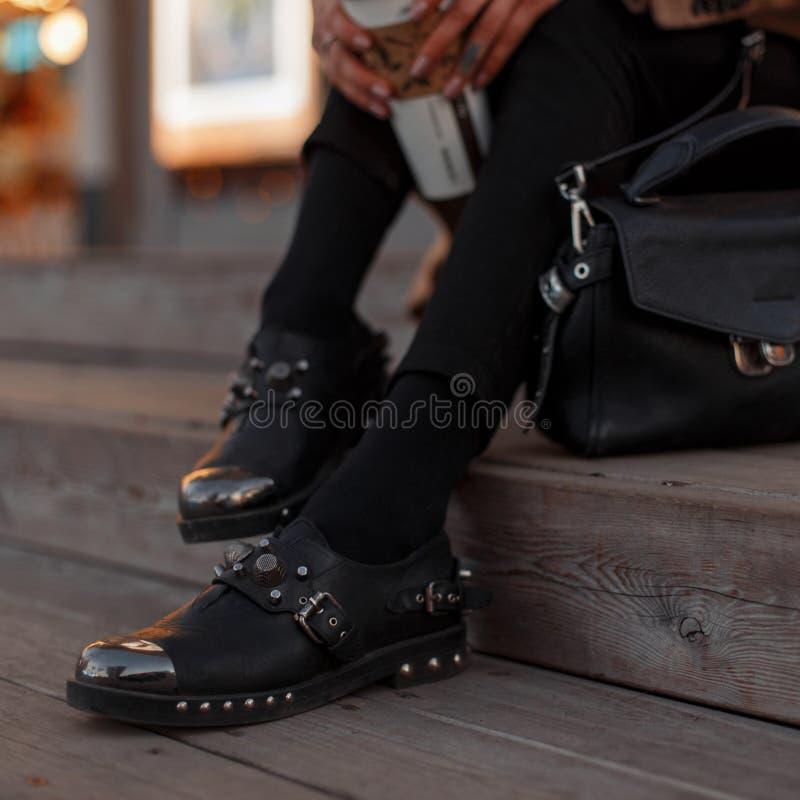 黑时兴的牛仔裤有一个时髦的皮革黑袋子的和黑皮革时兴的现代鞋子的少女 库存图片