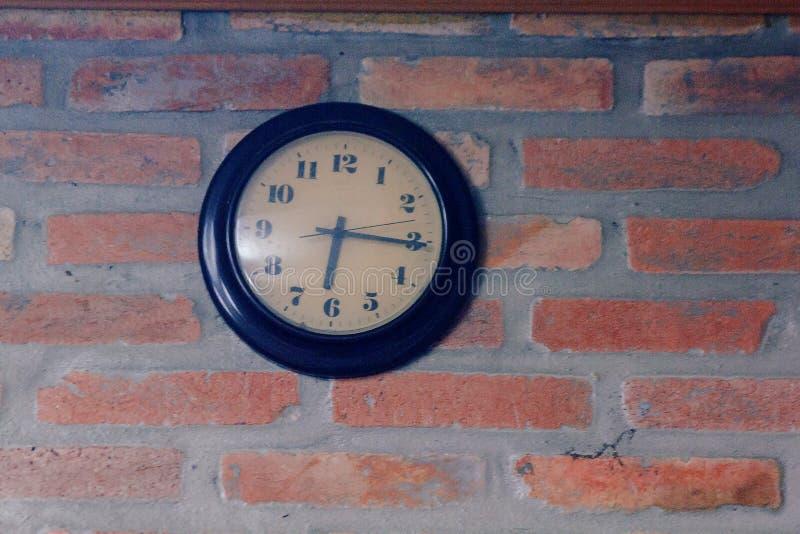 黑时钟在老砖墙上 免版税库存图片