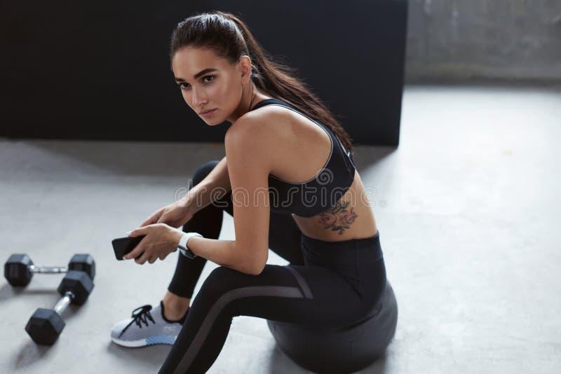 黑时髦的体育穿戴的妇女坐Med球 免版税库存图片