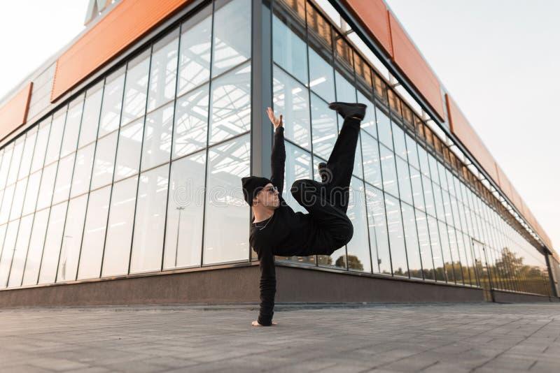黑时髦的衣裳的现代年轻专业人舞蹈家在时髦的太阳镜的一个被编织的帽子做着手倒立 图库摄影