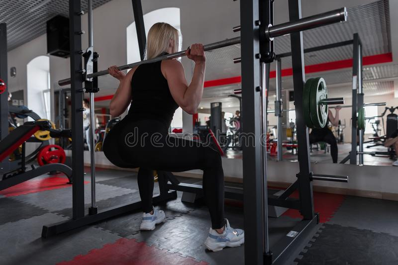 黑时髦的运动服的妇女在运动鞋蹲下与在肩膀的一只金属雕户内 做力量锻炼的女孩 免版税库存图片