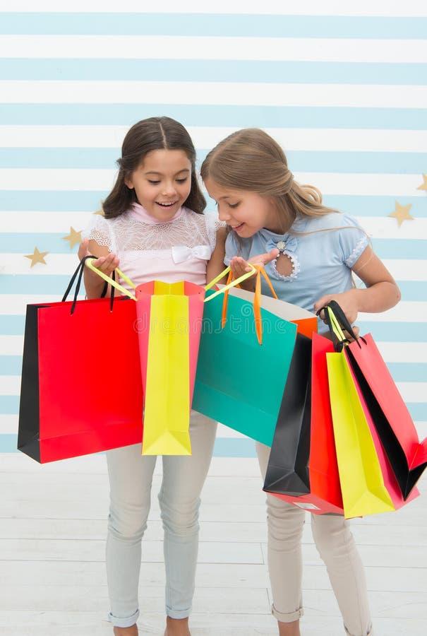 黑星期五在学校市场上 有购物袋的愉快的小孩子女孩在黑星期五销售以后 小孩子与 库存照片