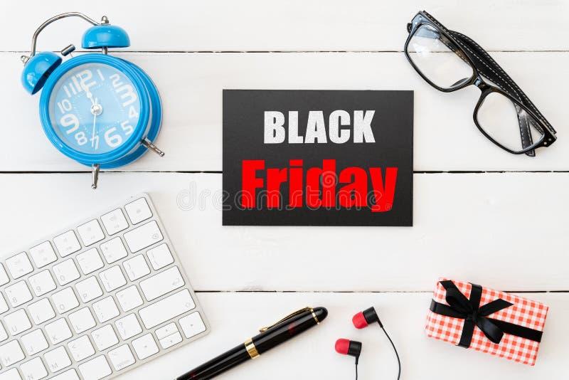 黑星期五销售文本在与礼物盒、玻璃、笔耳机和和闹钟的一个红色和黑标记和在白色木桌上 免版税图库摄影