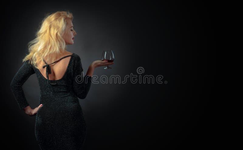 黑晚礼服的美丽的金发碧眼的女人与一口威士忌酒白兰地酒 免版税图库摄影
