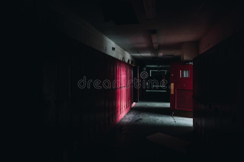 黑暗、阴暗的走廊+红色储物柜 — 废弃的格莱斯顿学校 — 宾夕法尼亚州匹兹堡 库存图片