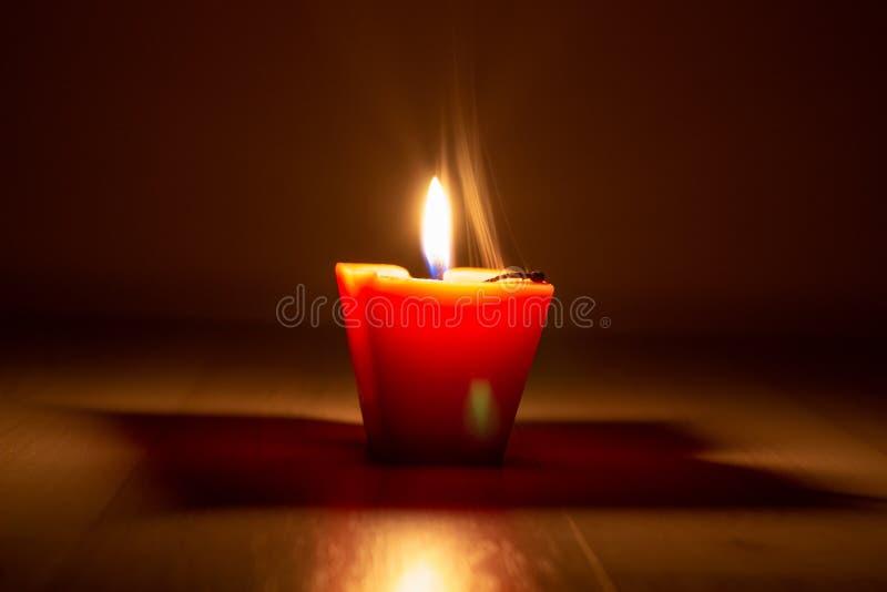 黑暗中,烟熏的黄色蜡烛从灯芯上落下 烛光灭火,白烟降临 免版税库存照片