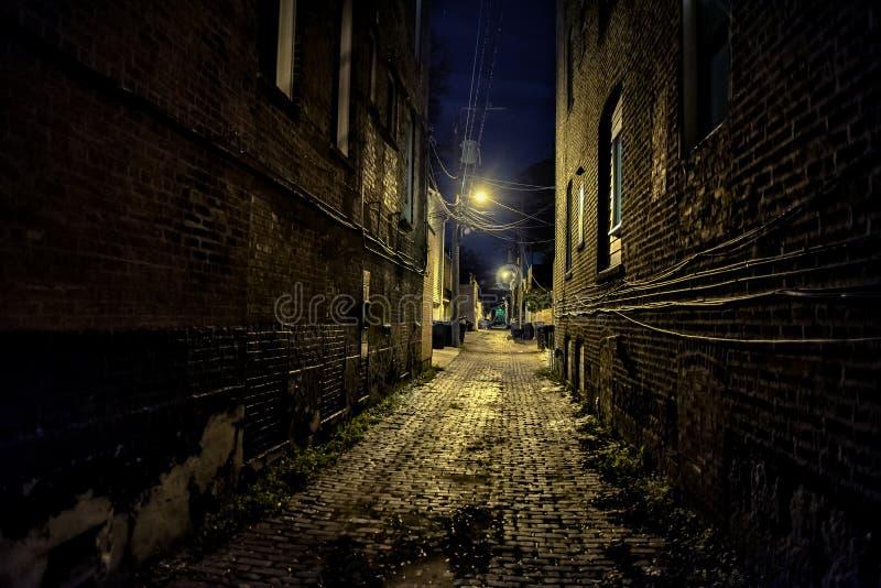 黑暗和令人毛骨悚然的都市城市鹅卵石砖胡同在晚上 免版税库存照片