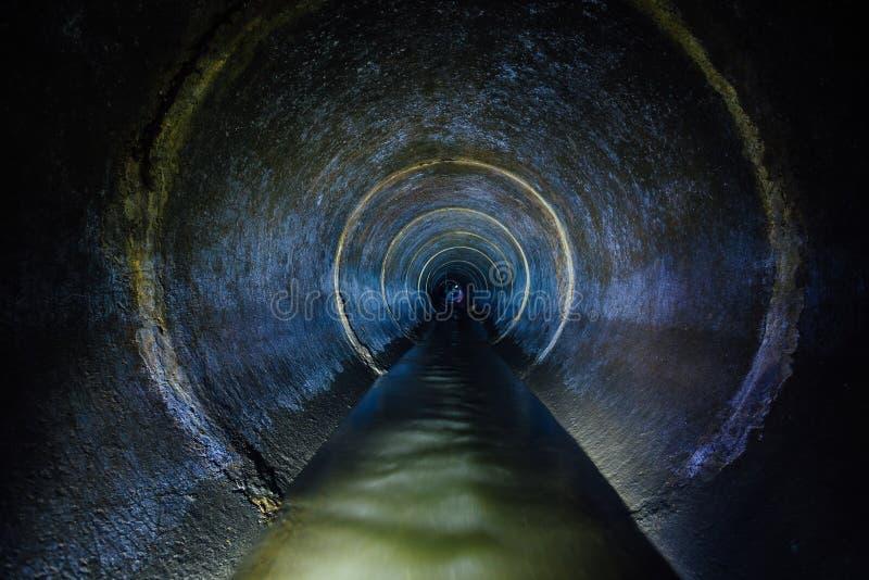黑暗地下下水道圆的具体隧道 工业污水和都市污水流动的投掷下水道 免版税库存照片