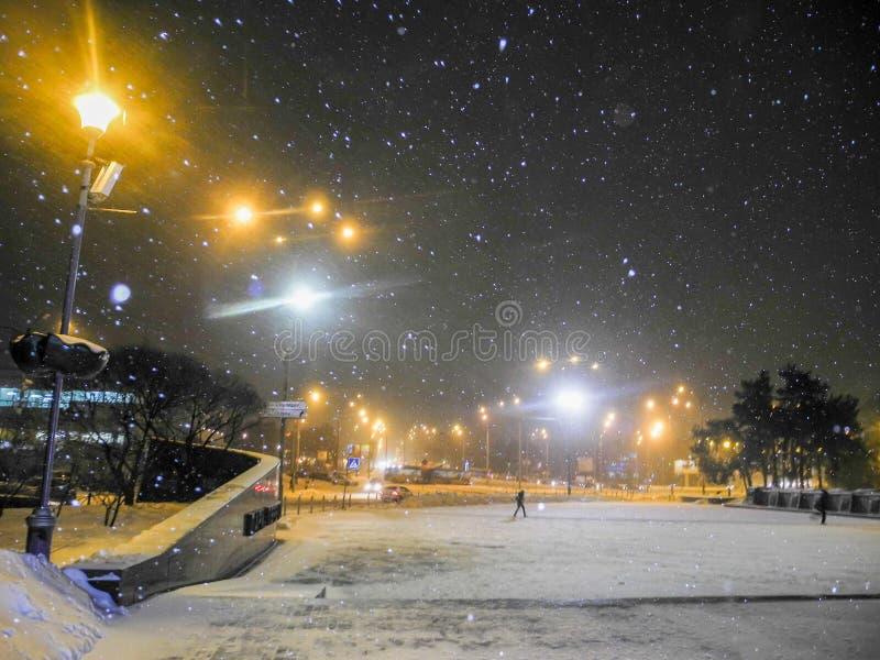 黑暗的冷淡的晚上公园冬天 降雪和橙色光灯笼 库存图片