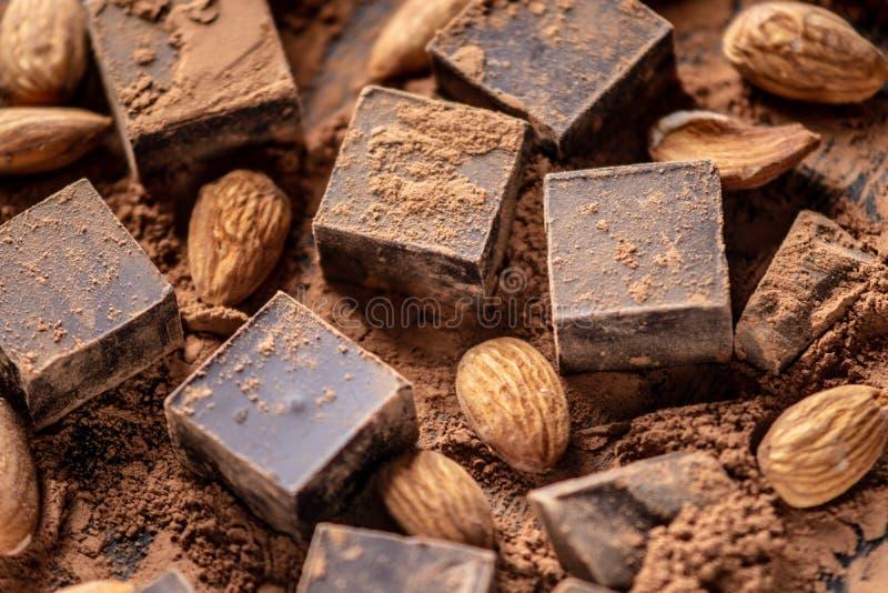 黑暗的可可浆片断与可可粉和杏仁坚果的在木背景 与空间的卡片文本的 免版税库存照片