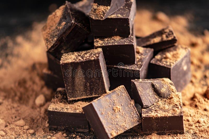 黑暗的可可浆片断与可可粉的在黑暗的木背景 糖果店成份的概念 免版税库存图片