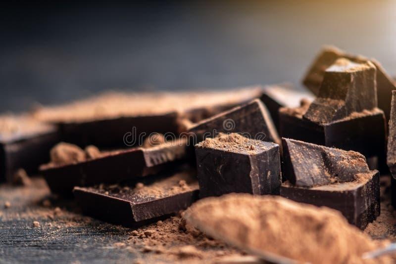 黑暗的可可浆片断与可可粉的在黑暗的木背景 糖果店成份的概念 免版税库存照片
