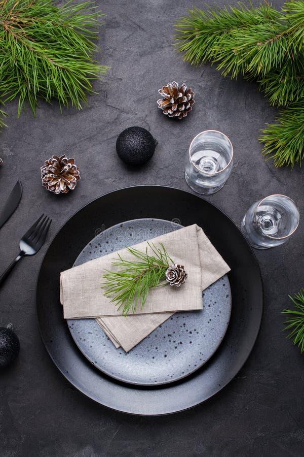 黑暗的圣诞节桌布景 黑色的盘子、香槟玻璃、叉子和刀子集合与餐巾,冷杉分支 免版税图库摄影