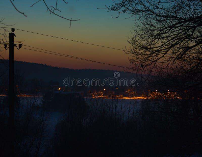 黑暗的城市在有晚日落的森林里 图库摄影