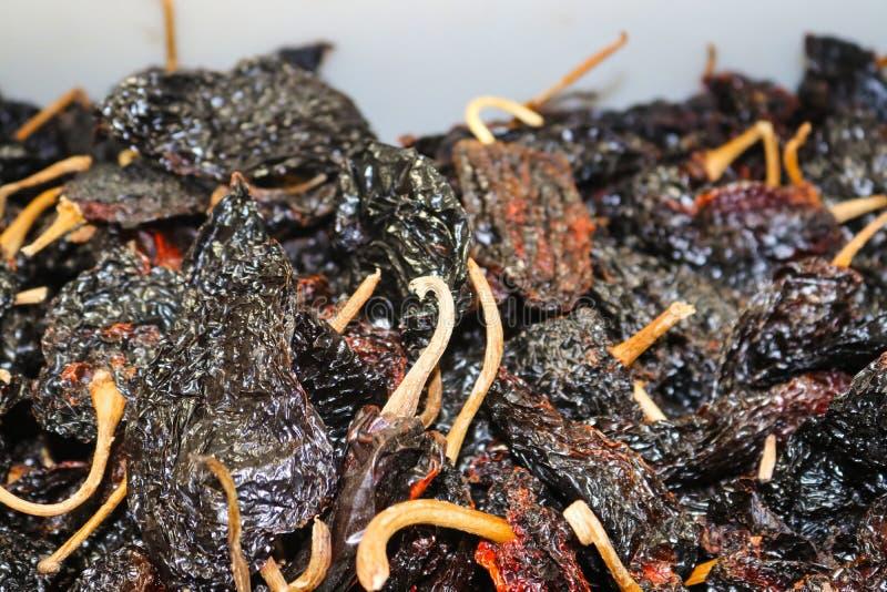 黑暗的墨西哥辣椒散装在市场-一温和上对媒介烘干了-是辣椒三位一体的一部分用于的Poblano 免版税库存照片