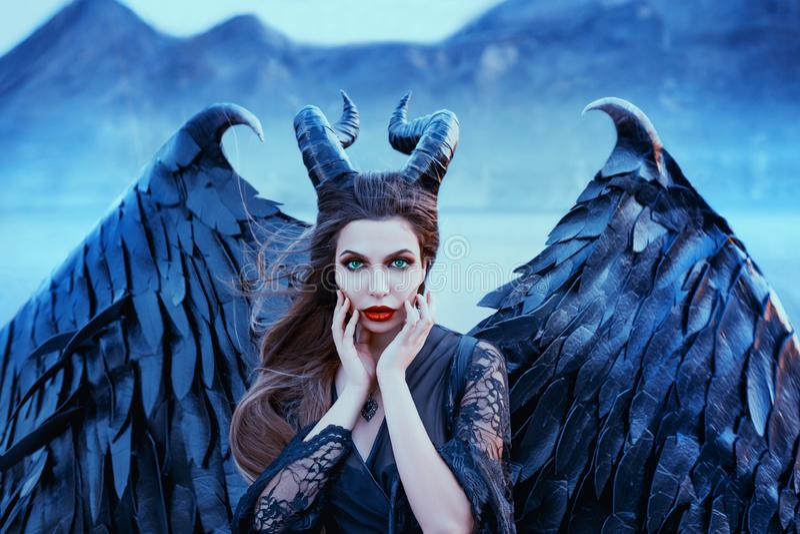 黑暗的天使迷人的画象与锋利的垫铁和爪的在强的强有力的翼,黑鞋带礼服的邪恶的巫婆 免版税库存图片