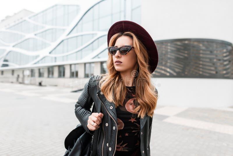 黑暗的太阳镜的华美的红发行家年轻女人在一时髦的黑皮夹克的一个典雅的帽子 免版税库存照片