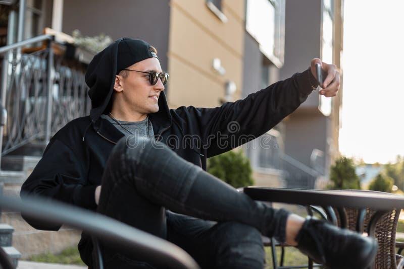 黑暗的太阳镜的快乐的行家年轻人在一有冠乌鸦的一个黑棒球帽在运动鞋的牛仔裤微笑并且采取selfie 免版税库存照片