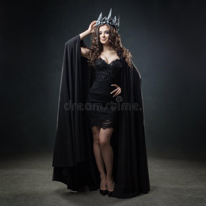黑暗的女王/王后 长的黑斗篷和冠的可爱和性感的年轻女人 免版税库存图片