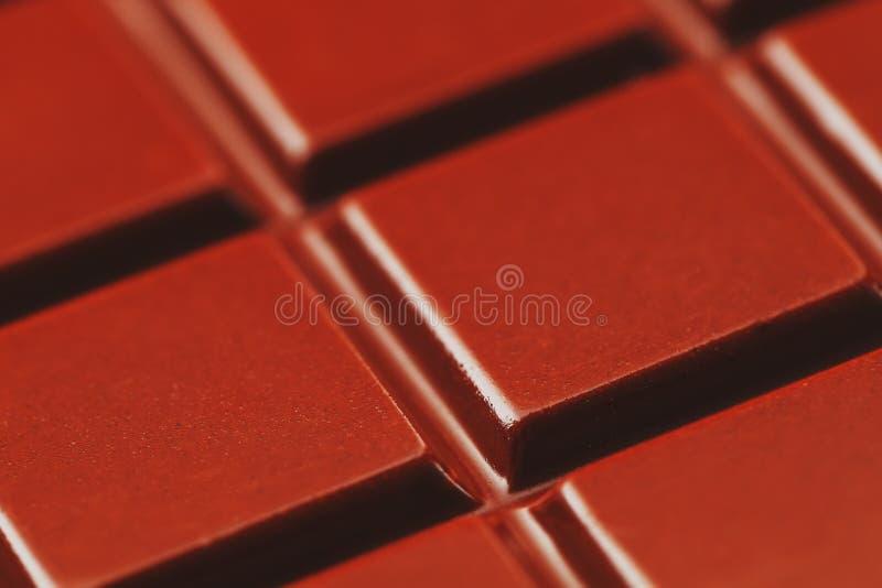 黑暗的巧克力关闭纹理  一个巧克力块的段在宏指令的 充分的框架纹理 免版税库存照片