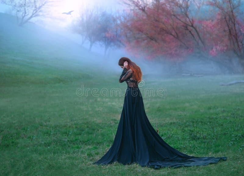 黑暗的巫婆犯了可怕的错误,长的黑礼服的哀伤的夫人有长尾巴和鞋带袖子的,有明亮的红色的女孩 库存图片