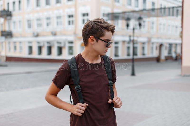 黑暗的时髦的太阳镜的年轻英俊的现代行家人在有背包的时髦夏天衣裳在城市走 免版税库存图片