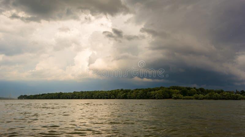 黑暗的暴风云有背景 在雷暴前的黑暗的云彩在多瑙河河沿  库存照片