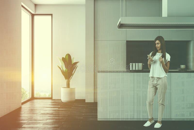 黑暗的木地板厨房,白色工作台面,妇女 免版税库存图片