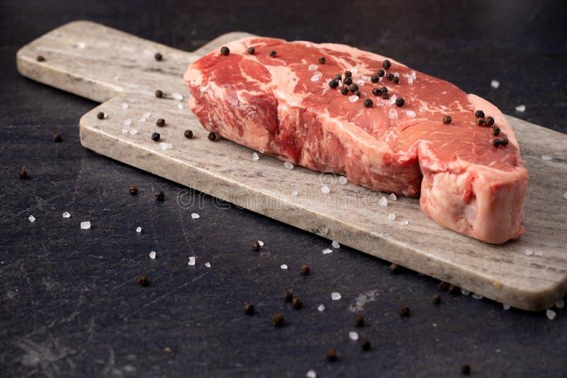 黑暗的板岩表面上的未加工的纽约小条牛排 免版税库存图片