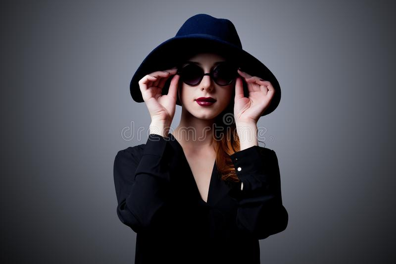 黑暗的样式的年轻红头发人女孩在太阳镜 库存图片
