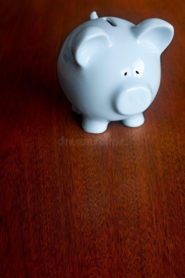 黑暗的橡木表面上的蓝色存钱罐 免版税库存图片