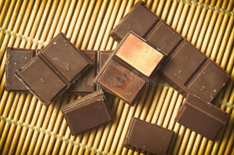 黑暗的牛奶巧克力酒吧片断在一个竹席子特写镜头的 免版税库存图片